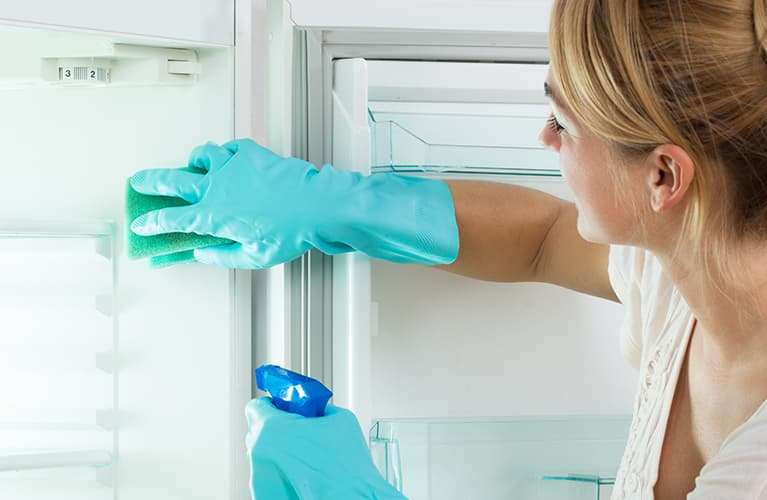Frau putzt Kühlschrank