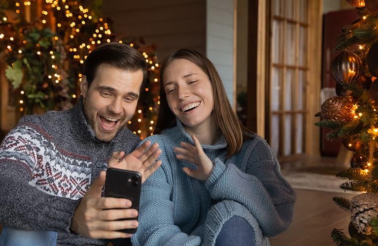 Pärchen, das glücklich ist - mit Weihnachtsbaum im Hintergrund
