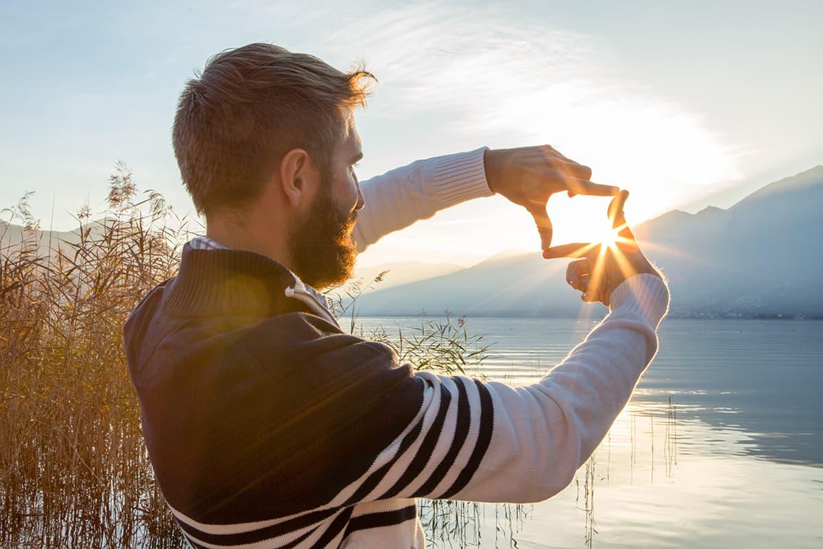 Stimmungs-Booster Sonne: Mann am See fängt mit den Fingern die Sonne ein