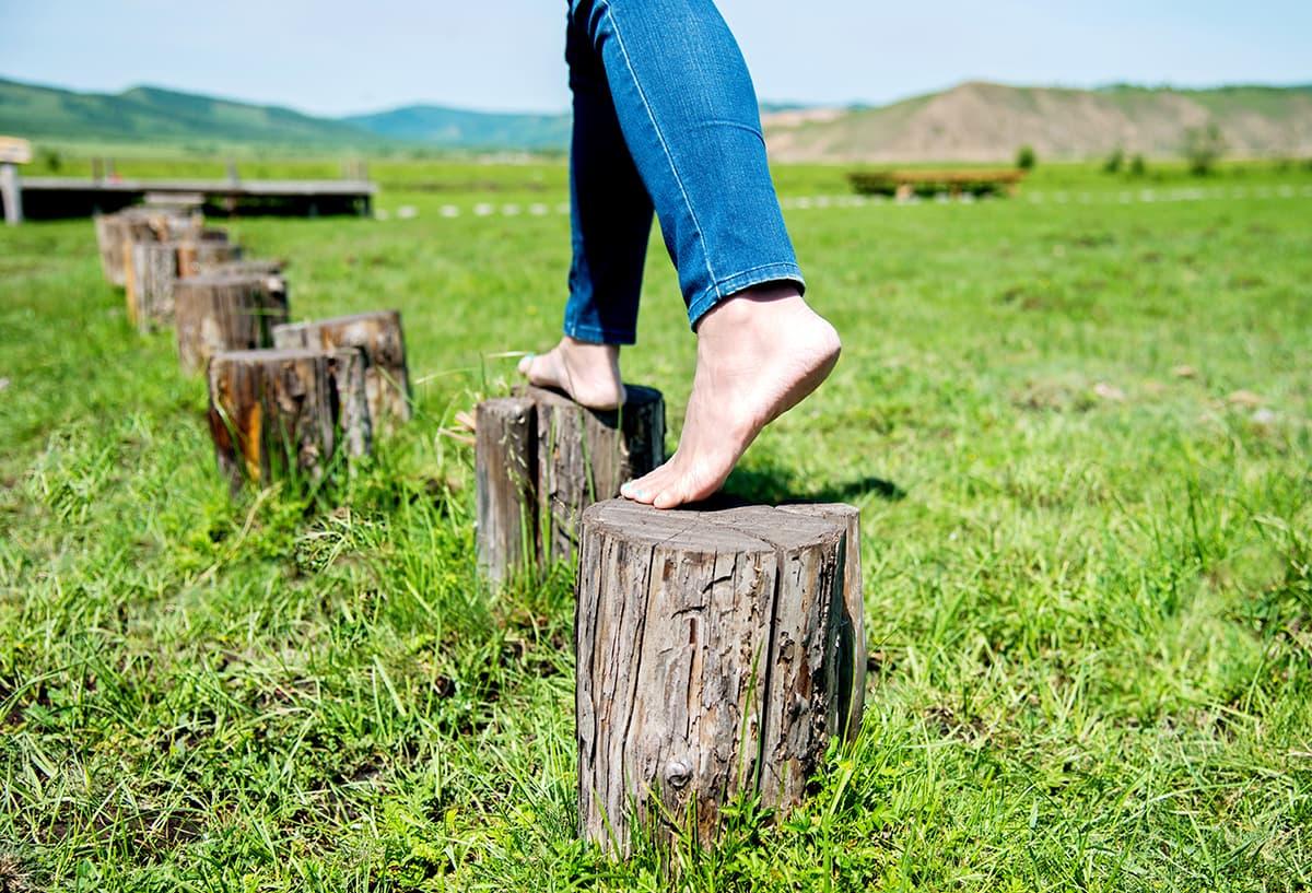 Sinne schärfen in der Natur: Nackte Füße balancieren über Baumstümpfe