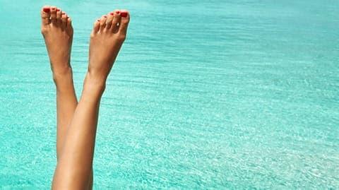 Frauenbeine mit Meer im Hintegrund