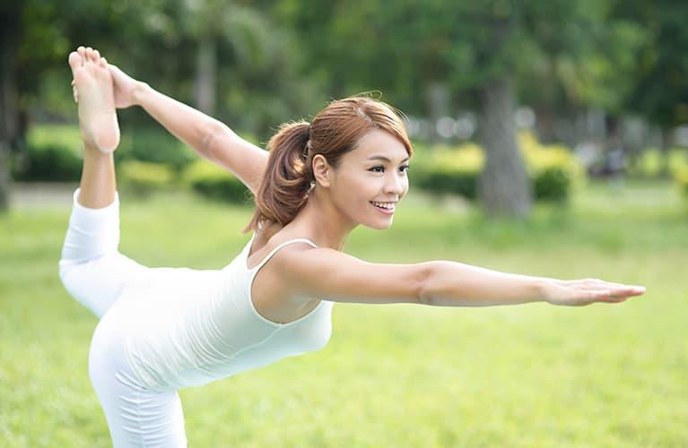 Eine Frau, die auf einer Wiese Yoga macht