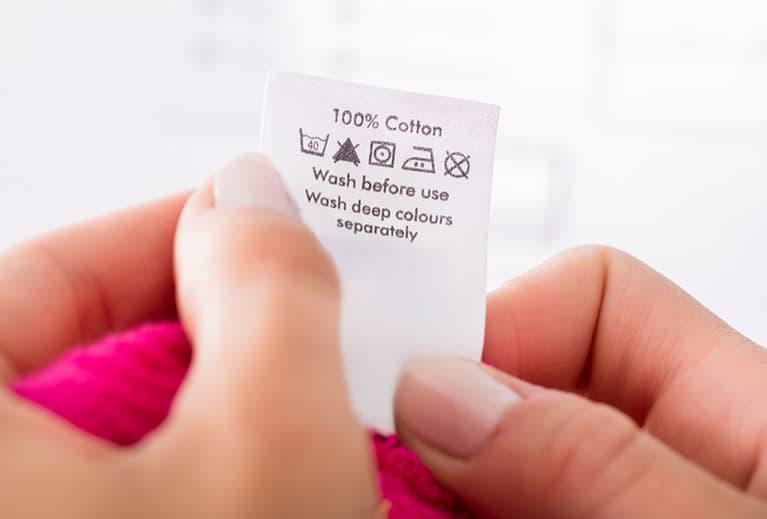 Frau hält ein Etikett mit Waschsymbolen in den Händen.