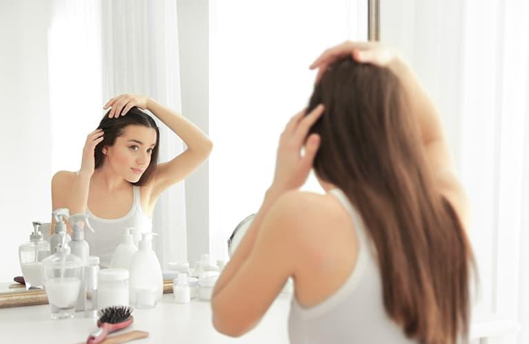 Haare pflegen: Eine langhaarige Frau prüft im Spiegel ihren Haaransatz
