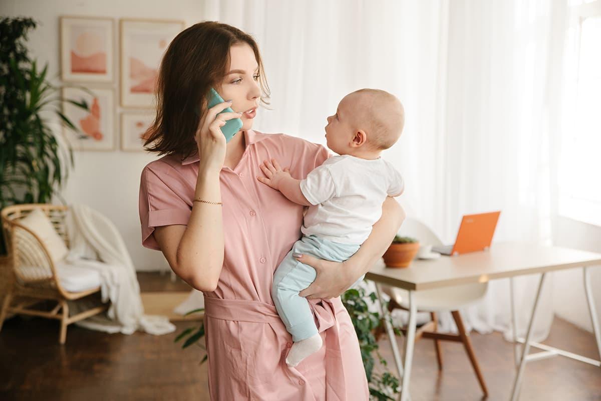 Mit Eltern-Tipps #GemeinsamStärker: Mutter mit Baby auf dem Arm am Handy.