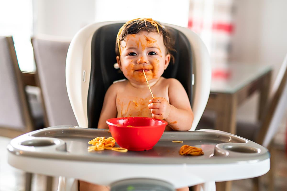 Mit Eltern-Tipps #GemeinsamStärker: Baby im Hochstuhl kleckert mit Essen.