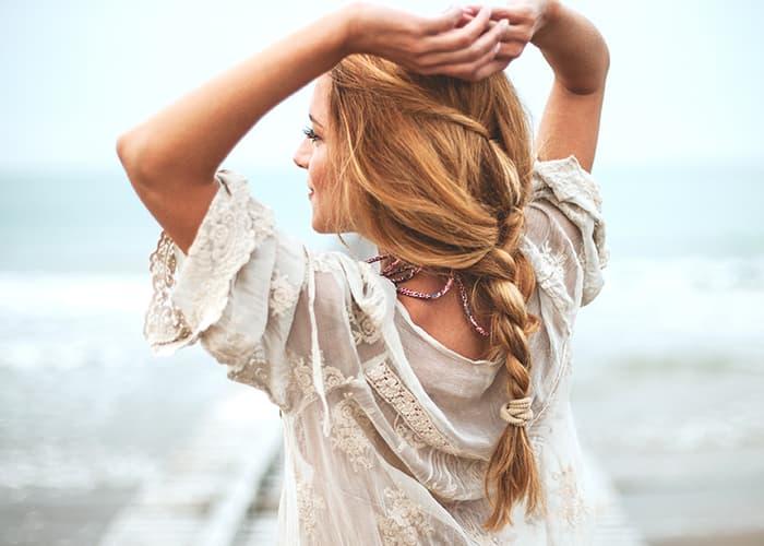 Junge, blonde Frau mit einer coolen, geflochtenen Sommerfrisur.