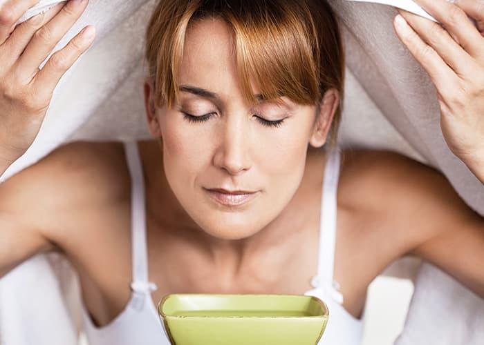Frau macht ein Dampfbad gegen verstopfte Poren.
