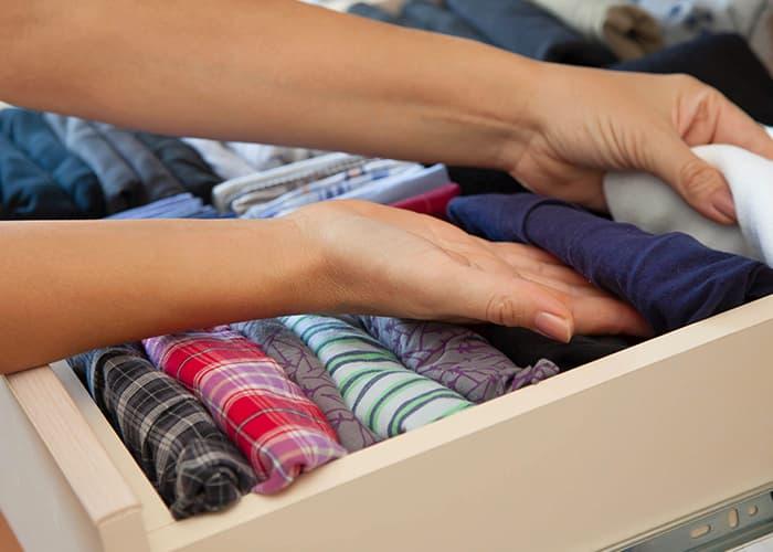 Frau räumt Schublade mit Kleidung ein, die nun voll ist. Mit Lenor bleibt die Kleidung trotzdem frisch.
