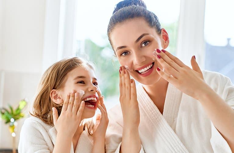 Mädchen mit ihrer Mama bei der Hautpflege
