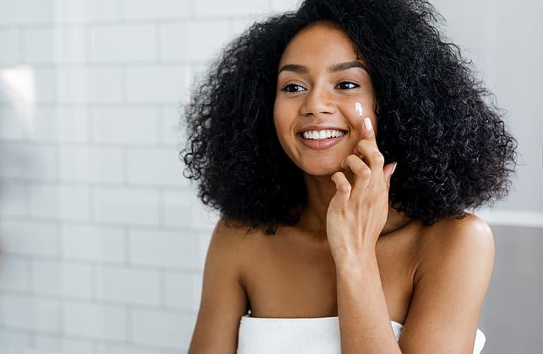 Junge Frau hat ihre beste Gesichtspflege gefunden und trägt sie vor dem Kosmetikspiegel sitzend auf.