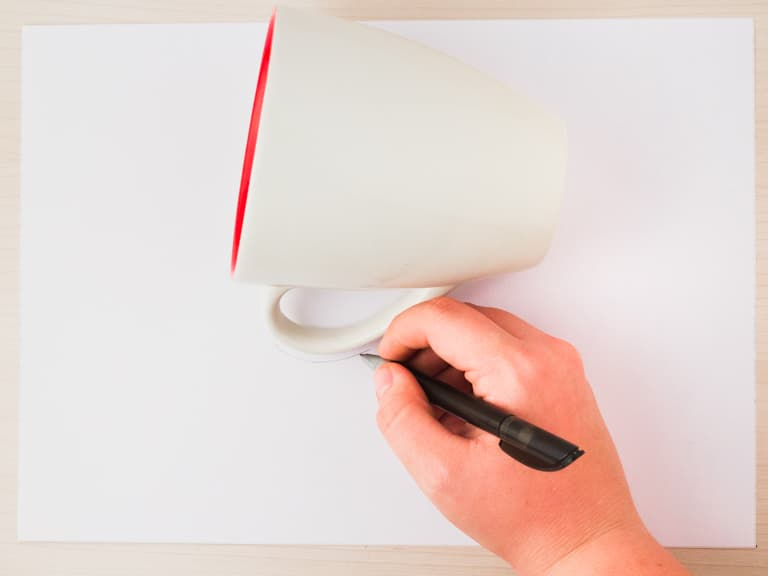 Een hand tekent de omtrek van de mok met een pen.