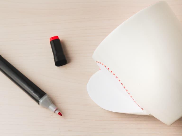 Een rode stift tekende stippen op de mok. Het kleefpapier wordt op de mok geplakt.