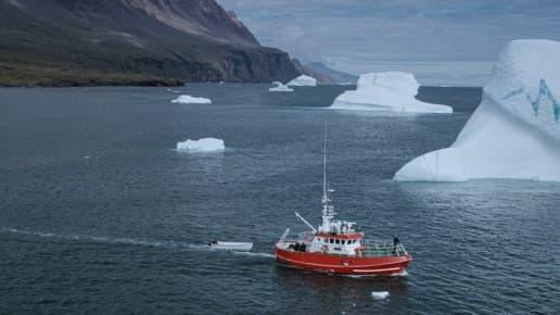 Martin Nielsen staat op de boeg van het onderzoeksschip Porsild terwijl het langs ijsbergen vaart voor de kust van Disko-eiland in West-Groenland.