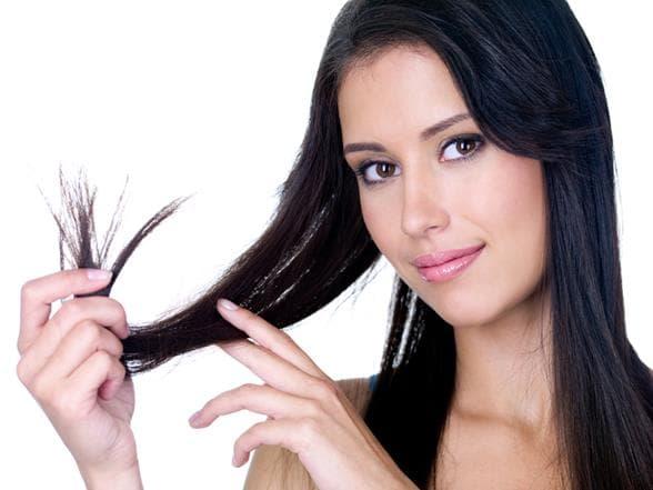 Une fille tient avec ses doigts ses pointes de cheveux