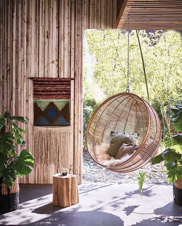 """Un mur en bois, un fauteuil """"boule"""" accroché par le haut, en extérieur"""