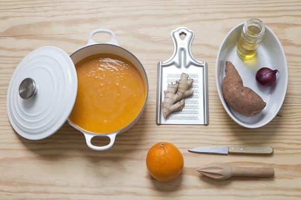 Une soupe au potiron dans une soupière avec un couteau, gingembre, de l'orange et une patate douce