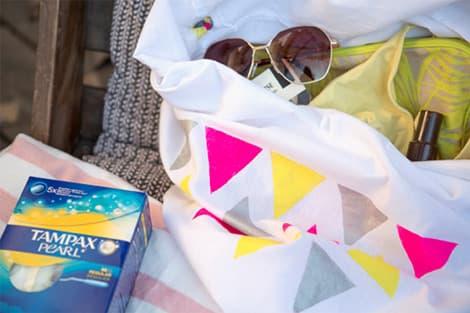 Le sac créé avec une paire de lunettes de soleil et des accessoires posés sur un transat, avec boite de tampax.