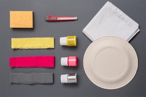 Une éponge, un cutter, du tissu, des colorant, des serviettes en papier et une assiette en carton.
