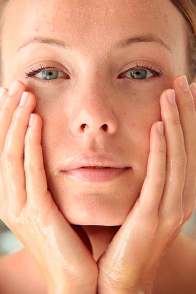 Een vrouw kijkt naar ons terwijl ze haar gezicht schoonmaakt.