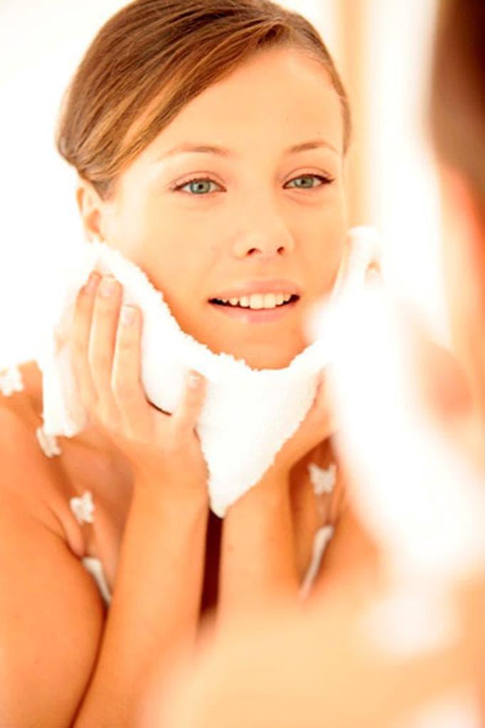 Een vrouw veegt haar gezicht af met een witte handdoek.