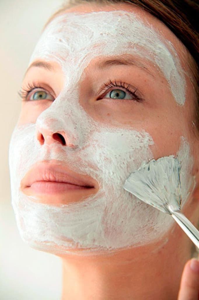 Een vrouw brengt crème op haar gezicht aan met een kwast.