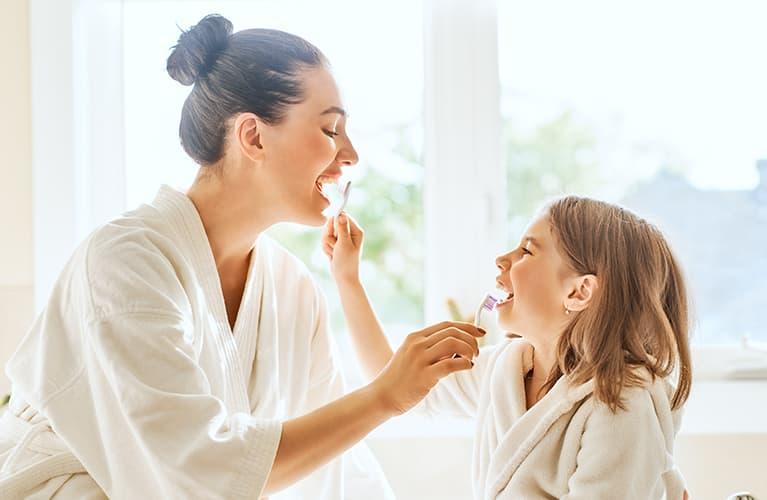 Mutter und Tochter putzen sich gegenseitig die Zähne mit Bürste und Zahnpasta.