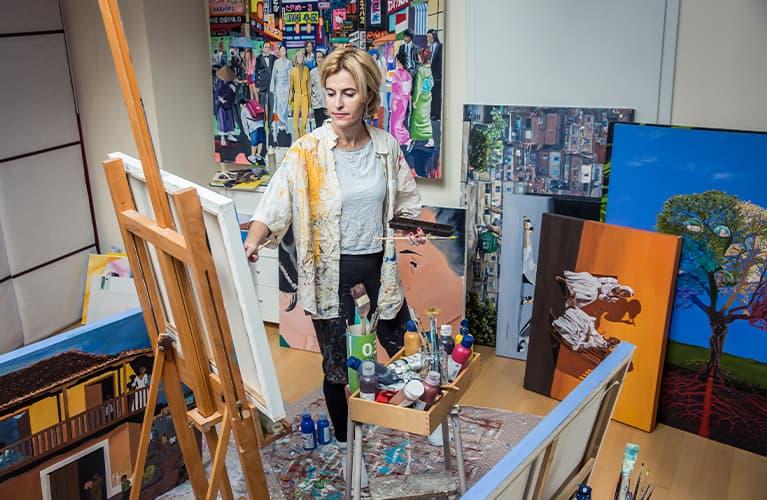 Frau malt eigenes Bild auf die Leinwand