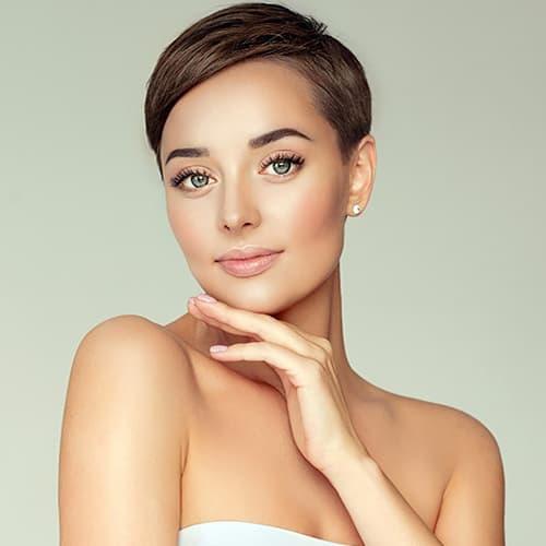 Frau im eleganten silbernen Kleid und mit langen Locken wirft einen Handkuss: Festliche Frisuren sorgen für ein besonderes Gefühl an Festtagen.