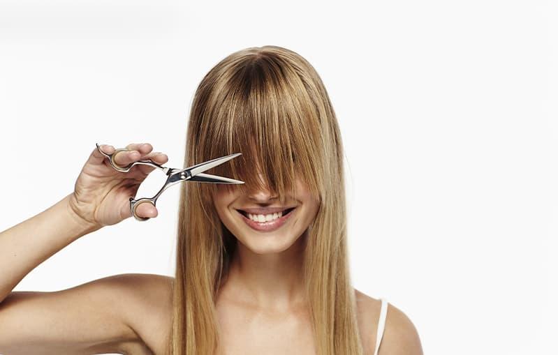 Haarpflege: Frau schneidet ihren Pony