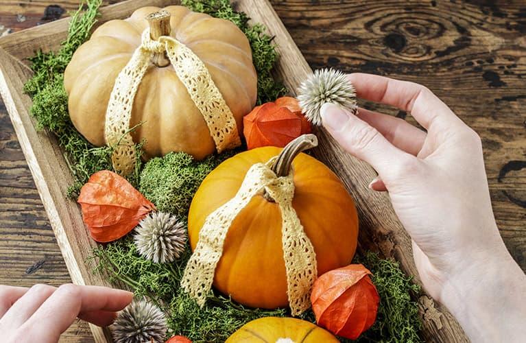 Tischarrangement aus unterschiedlichen Kürbissorten, Lampionblumen, Disteln und Moos