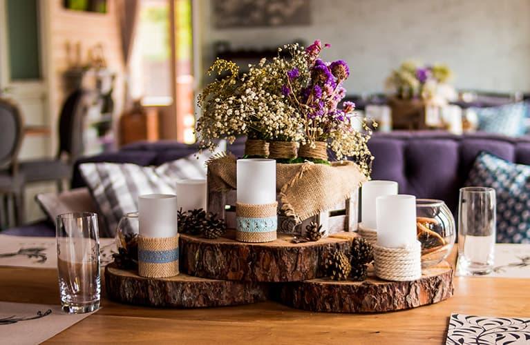 Tischarrangement aus Holzscheiben, Kerzen und getrockneten Blumen