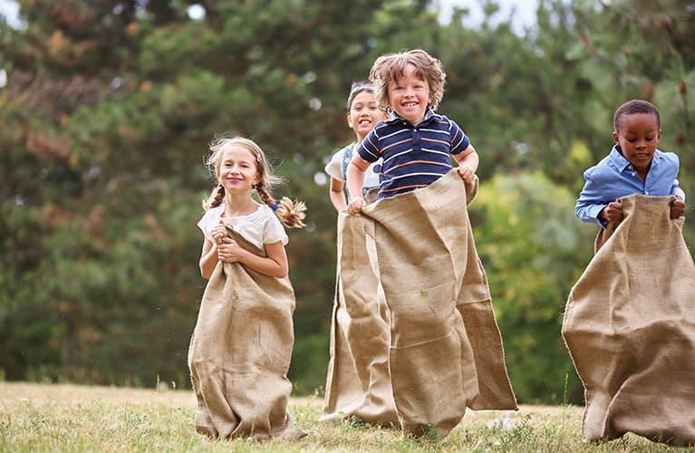 Gruppe von Kindern beim Sackhüpfen