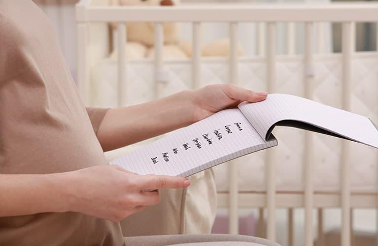 Schwangere Frau mit Block, Stift, Babyschuhen und Ultraschallbild überlegt sich Jungennamen und Mädchennamen