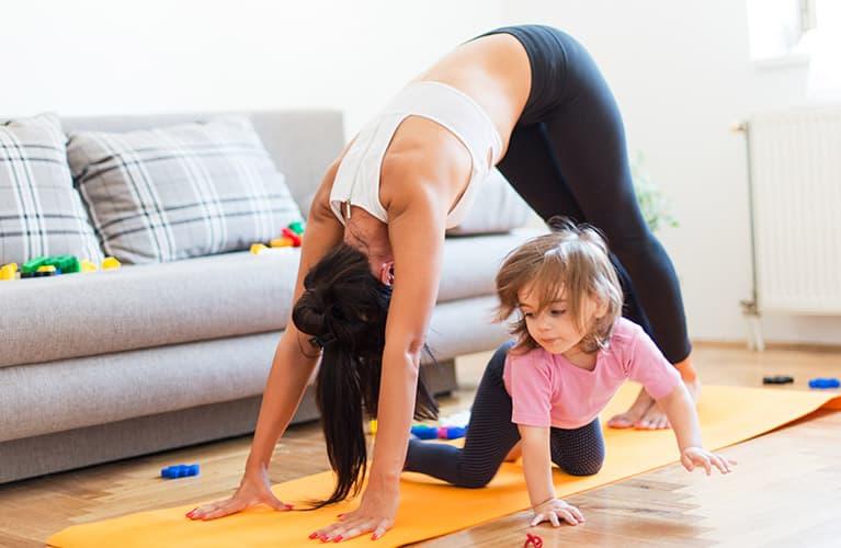 Frau mit Kind auf ihrer Yogamatte