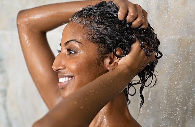 Eine Frau wäscht sich unter der Dusche die Haare.