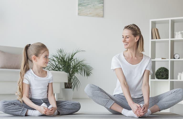 Frau mit Kind die Yoga machen