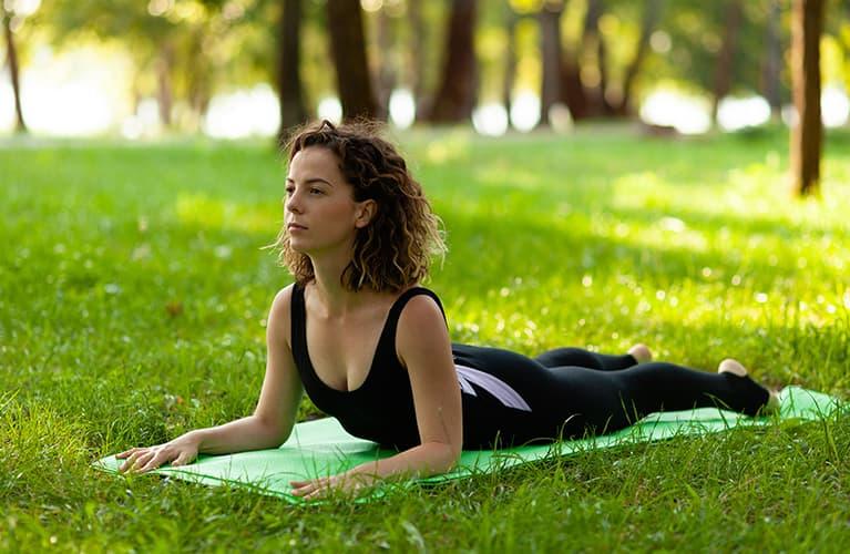 Frau die im freien Yoga macht