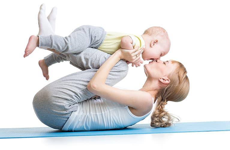Junge Mutter mit ihrem Kind beim Baby-Yoga