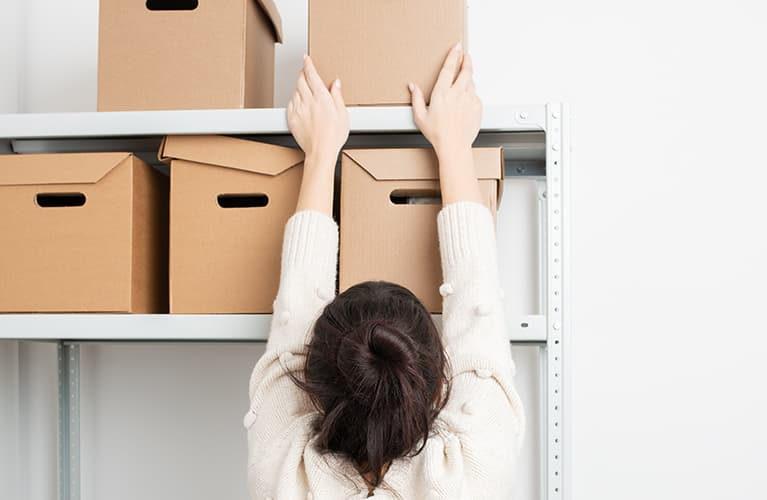 Keller entrümpeln: Ein Paar packt Kisten.