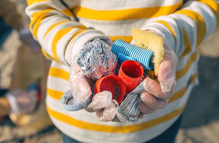 Kinderhände, die Müll in den Händen  hält
