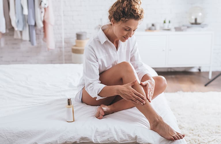 Auf einem Sofa angewinkelte schöne Beine einer Frau.