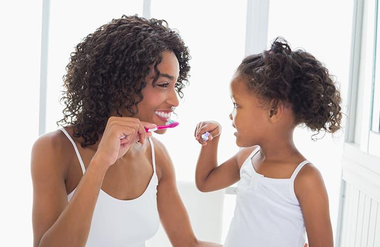 Eine Frau und ein Kind putzen Zähne.