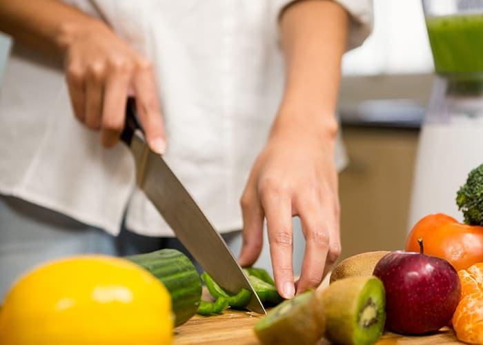 Zahngesunde Ernährung: Frau schneidet Paprika, Gurke, Kiwi & Co.