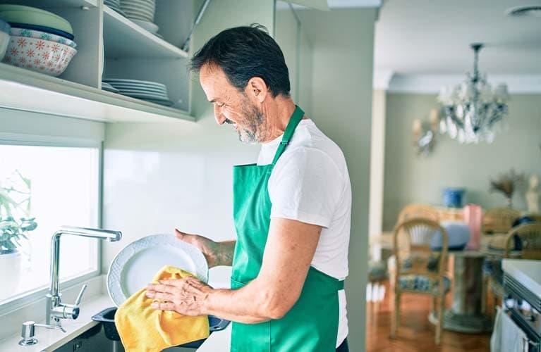 Mann steht in der Küche und wäscht das Geschirr ab