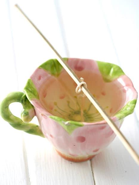 Passo 4, coloque o fio na taça de chá com a cera ainda líquida.