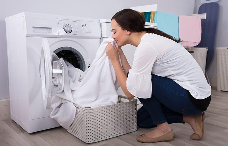 Κυρία με πλυντήριο ρούχων και πλυμένα ρούχα