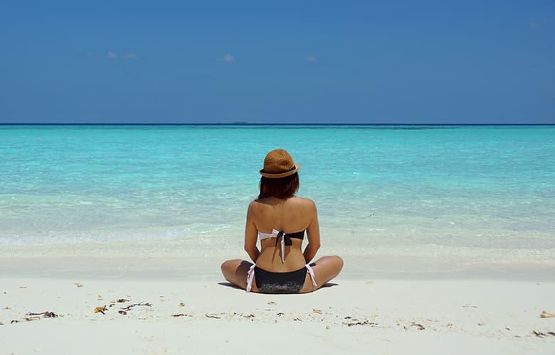 Γυναίκα στην παραλία κοιτάει τη θάλασσα